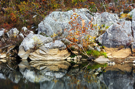 Layered rock sits on the Buffalo River shoreline. It is mirrored in the still waters, and surrounded by Fall foliage.