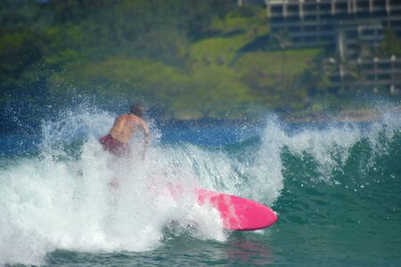 off cuts: Gaining momentum, surfer and his bright pink surfboard, cuts through a wave as the spray covers him, off the coast of Kauai, Hawaii. Stock Photo