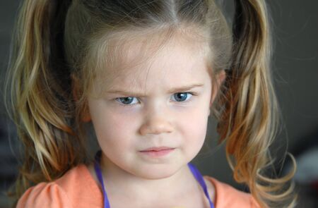 irritated: Closeup photo of little girl shows her furrowed brow and irritated frown.