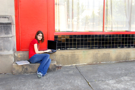 junior high: Young junior high student sits on steps of school and researches her homework on her laptop.  She has on a red shirt and jeans.