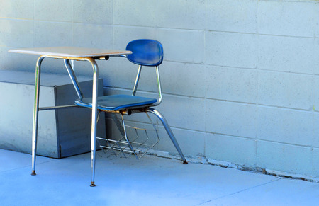 Rusting metal school desk sits in alley behind school.  It has been replaced by newer equipment and has been left to rust.