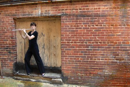 grungey: Street musician, female dressed in black, plays her flute in a back street alleyway.  She is standing in front of a sealed off doorway.