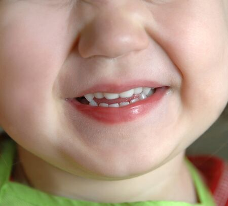 mouth close up: Image shows extreme closeup of a little girl who is smiling and happy.  Photo shows chin, mouth and nose area.