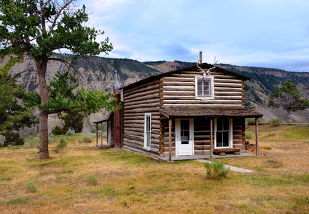 Early mail carriers cabin sits in the area of Mammoth Springs in Yellowstone National Park.  Cabin is two stories and sits on the edge of cliff.