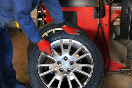 rag wheel: Worker at a tire store, rubs and polishes a chrome rim on a wheel.  He is wearing red gloves and holding a rag.