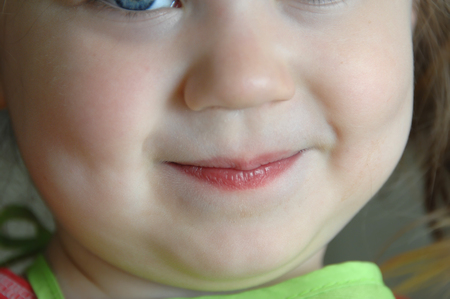 grinning: Little eye peeks into image.  This small girl is grinning mischeiviously.  Closeup image.