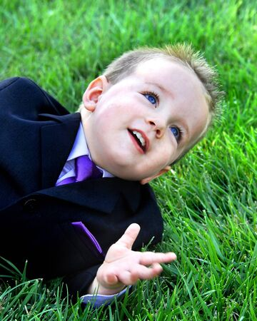 Little boy lays in the grass, wearing a tuxedo with purple tie, and explains how life should go.  His hand is moving as he talks.