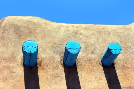 adobe: Roofline of adobe home in Taos, New Mexico, shows turquoise painted timbers.