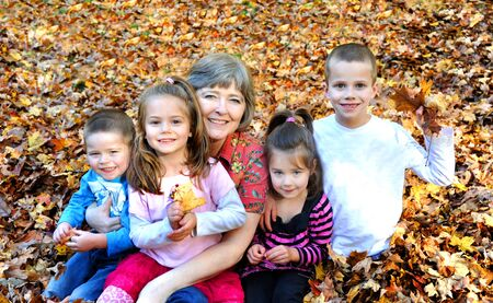 Raking leaves and having some fun is this family's tradition.  Grandmother holds two of her grandkids and the other two sit besides her.  They are buried in leaves. photo