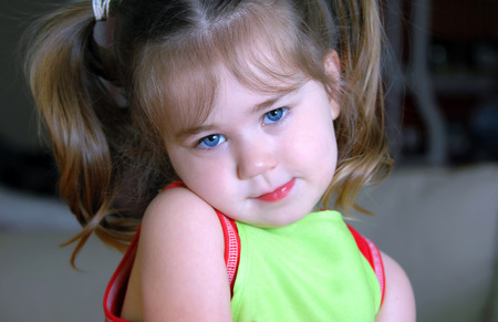 bashful: Little girl hides her chin on her shoulder and looks shyly at the camera.  Closeup shot of just her head and shoulders. Stock Photo