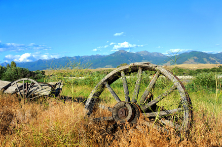 pioneers: Wagon and wheels lay abandoned in deep grass along the highway in Paradise Valley, Montana.  The Absaroka Mountains loom in the distance.