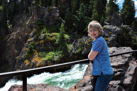 brink: Senior traveler leans on the rail besides the brink of Upper Falls in Yellowstone National Park.  She is smiling and enjoying the beautiful view as the water pours over the cliff.