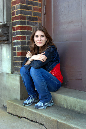 hint: Young high school sudent sits on the steps of her high school building.  She is solemn with just a hint of a smile.  She is wearing jeans and a denim jacket.