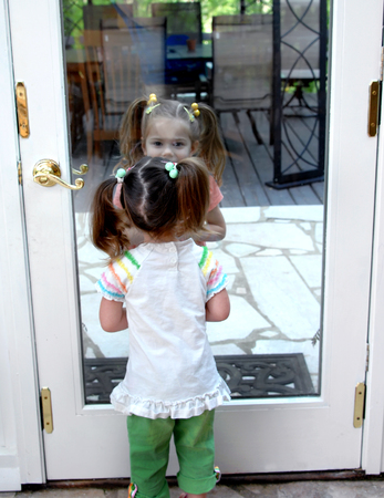sibling rivalry: Two children illustrate on the outside looking in, or transparent, or looking glass.  One child is standing outside and the other inside. Stock Photo