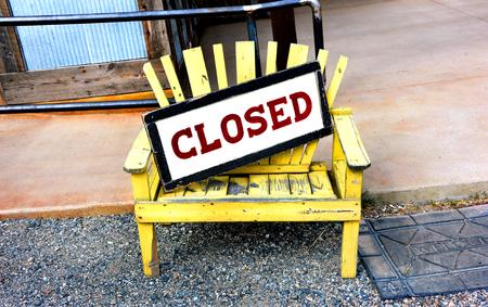 Een gele houten bank zit naast een welkome mat in de voorkant van een cafe. De tegenstellingen komen met een bordje op de bank dat de staten gesloten. Het concept van welkom en gesloten duel.