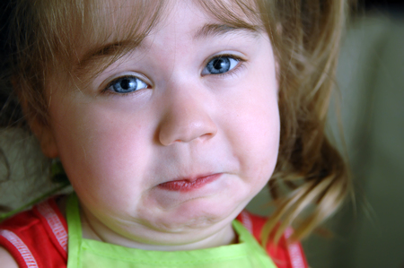 Little girl wrinkles her face up in a frown from something smelling aweful.  Image shows closeup of her face.