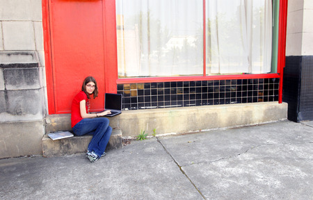 junior high: Young junior high student sits outside school buildng working on her homework.  She has a laptop and books.  She is wearing jeans and red shirt. Stock Photo