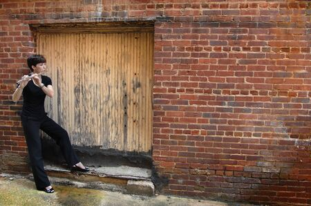 Female Street Musician, dressed in black, stands in closed and sealed doorway of an alley and plays her flute.  She is leaning against a brick wall in downtown USA.
