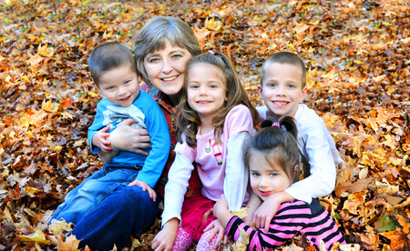 grandkids: Raking Autumn leaves, this grandmother stops to hug up all her grandkids.  They are sitting in a pile of leaves and smiling happily.  The children include two boys and two girls.