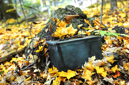 caching: Military ammunition box is used for this geocaching activity.  It sits camouflaged on the forest floor covered with Autumn leaves. Stock Photo