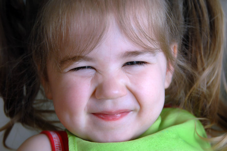 Beaming face of little girl, shows her teasing personality.  Her eyes are scrunched and her lips are grinning. Stock Photo