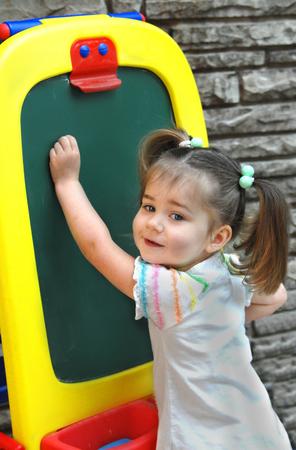 小さな女の子は、チョーク ボードに書くことによって学ぶことを開始します。 彼女は白いシャツを着て、カメラに笑顔します。 チョーク ボードは 写真素材