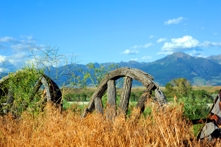 days gone by: Overgrown wagon wheels represent days gone by when the west brought settlers by wagon to this Paradise Valley in Montana.  Absaroka Mountains loom in distance. Stock Photo