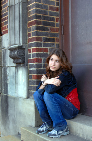 lost in thought: Young high school student sits on the steps of her school and is lost in thought.  She is wearing a denim jacket and jeans. Stock Photo