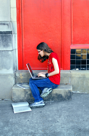 lap top: Young high school student holds a lap top as she sits on the steps of her school.  She has her books at her feet and is doing research on a homework paper. Stock Photo