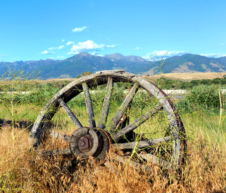 pioneering: Wagon and wheels lay abandoned in deep grass along the highway in Paradise Valley, Montana.  The Absaroka Mountains loom in the distance.