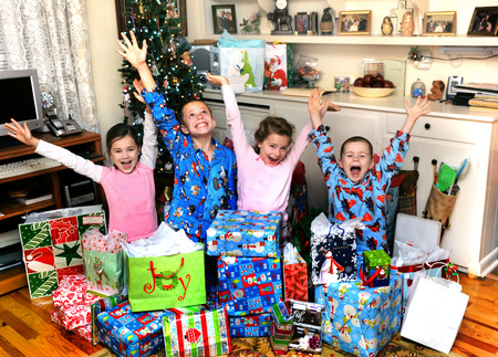 Four small siblings celebrate their joy on Christmas morning by yelling and shouting happily.  They are sitting in front of the Christmas tree in their home. photo