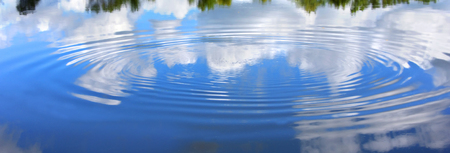widening: Disturbance in the Yahara River causes a ripple to grow on its surface.  Vivid blue sky and fluffy clouds reflect on smooth surface. Stock Photo