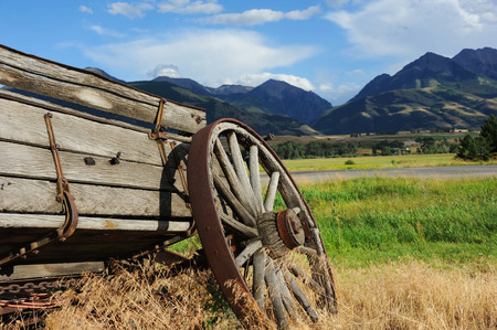 relics: Broken down wagon is one of the few relics of the west.  Wagon faces the mountains surrounding Paradise Valley in Montana.  Weeds and grass grow around wagon. Stock Photo