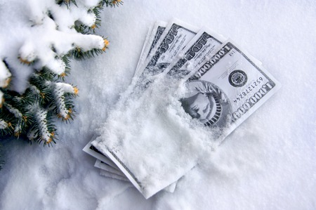 stash: Pile of play money is covered with snow.  Fir branches frame stash of money. Stock Photo
