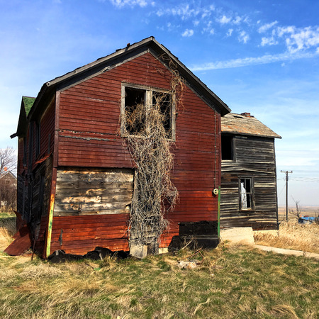 Deserted and derelict farmhouse on the plains in South Dakota has weathered red wood and overgorwn with weeds.  Weeds are growing out of the broken windows. Stock Photo