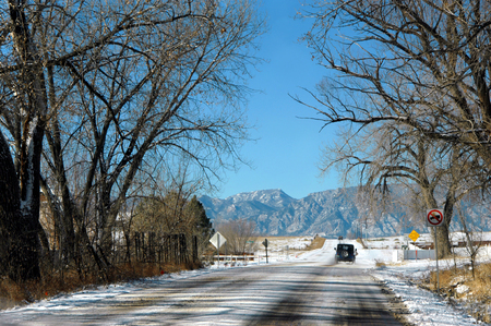 colorado rockies: Automobiles travel along icy road heading toward the scenic Rocky Mountains outside of Colorado Springs. Stock Photo