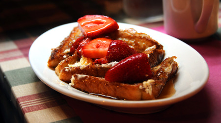 Delicious breakfast of french toast topped with strawberries and syrup, sit on a rustic table besides a cup of coffee. Stock Photo