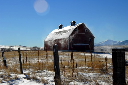 Snow blows from the roof of a rustic, wooden barn in Colorado.  Pole fence runs in front of barn.  Light coat of snow sits on roof and pasture. Stock Photo