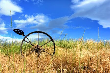 spokes: Antique horse drawn plow, sits abandoned in a field in Hapy Valley, Wyoming.  Metal plow has seat and metal wheel with spokes. Stock Photo