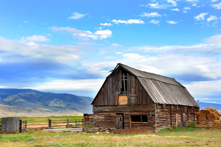 disrepair: Rustic log barn has wooden roof and is in disrepair.  Field behind barn rolls across the distance to the mountains of Paradise Valley, Wyoming.