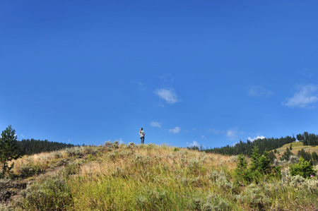 vastness: Young woman climbs a hillside overlooking Yellowstone National Park.  The lofty perch affords her a better view of the vastness of Yellowstone.