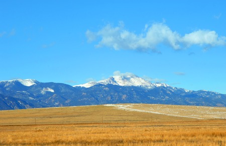 View of Pikes Peak in the Colorado Rocky Mountains.  Golden field fronts mountains.