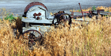 wood agricultural: Agricultural relic sits overgorwn in weeds.  It is composed of wood and metal and sits in Happy Valley, Wyoming.