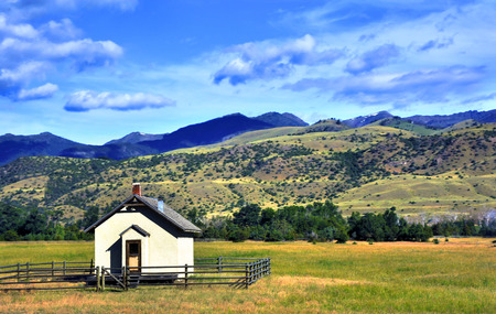surrounds: Tiny one room school house sits on the valley floor in Paradise Valley.  Wooden fence surrounds school and Gallatin Mountains rise in the back.