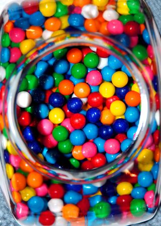 gumballs: Glass jar is open and reveals a pile of multi-colored gumballs. Reach in a grab a handful. Stock Photo