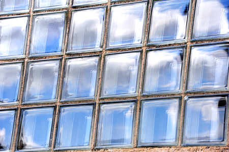 window panes: Background image shows sky reflected in rectangle panes of glass.  Window is made of individual panes of thick glass.