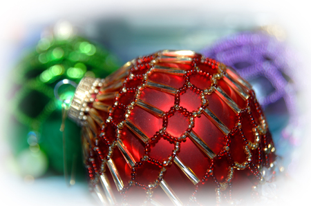 surrounds: Soft white light surrounds homemade Christmas ornaments.  Beads decorate red and green balls.