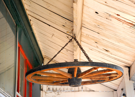 Old, wood wagon wheel is recycled and used as decoration.  It is hanging in the eaves of an old house in Wyoming. Stock Photo