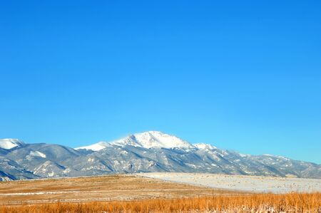 Blue, morning skies frame Pikes Peak in the Colorado Rocky Mountains.  Golden field is in foreground.