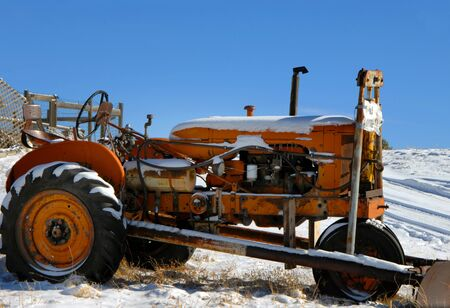 snow plow: Orange tractor sits outdoors in the weather.  Snow sits on tires and hood.  Snow plow is attached. Stock Photo